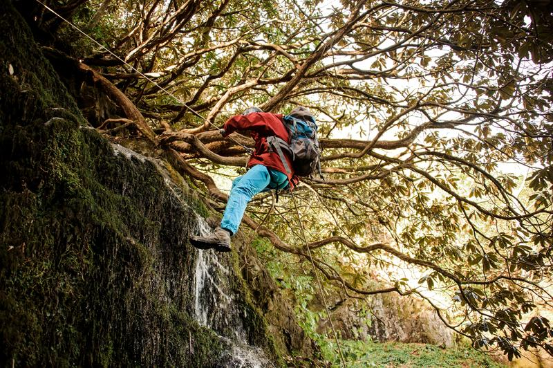 Young man dulfers down the mountains with waterfall in Adjara. Young man in a red jacket with backpack dulfers down the mountains with trees and small beautiful royalty free stock photos