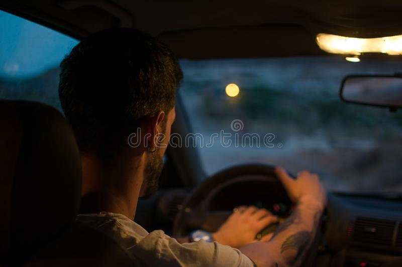 Young man with earrings drives a car at night royalty free stock photography