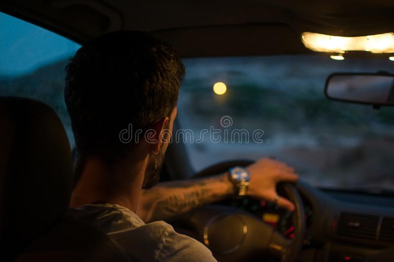 Young man with earrings drives a car at night stock photo