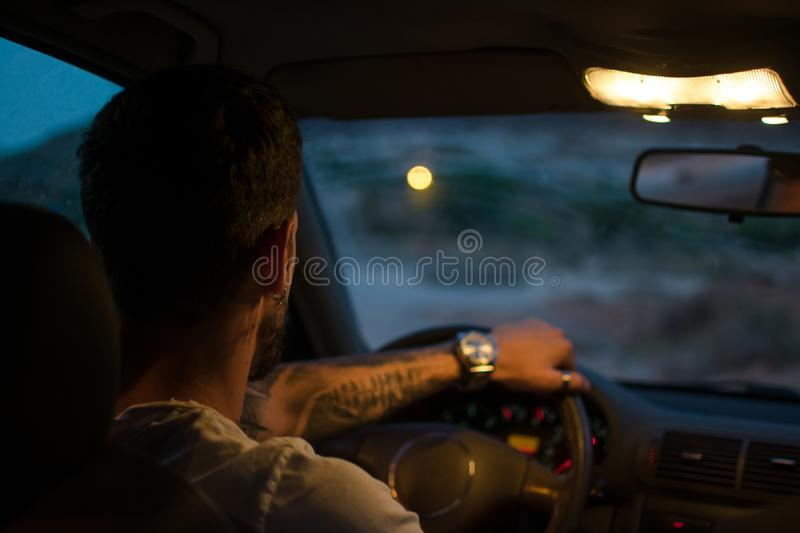 Young man with earrings drives a car at night royalty free stock photos