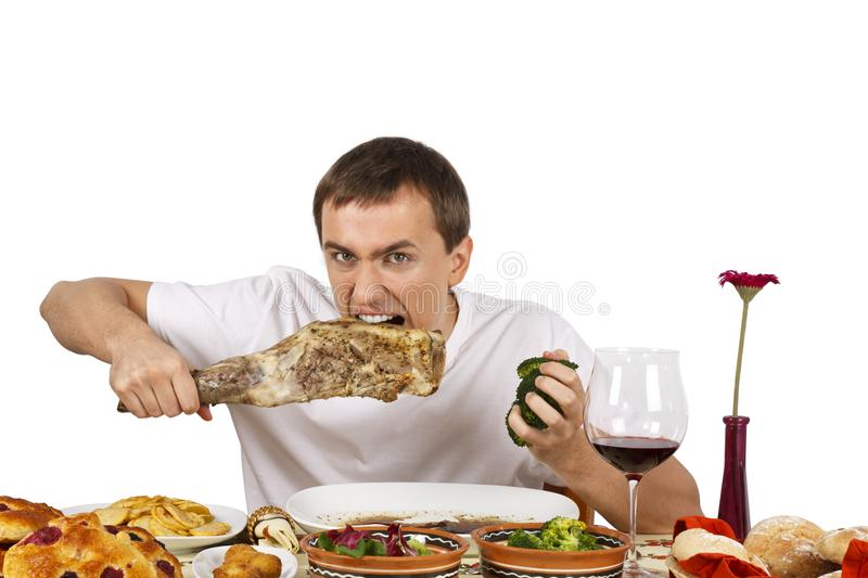 Young man eating. Bad mannered young man eating a leg of lamb. Isolated of white background royalty free stock image
