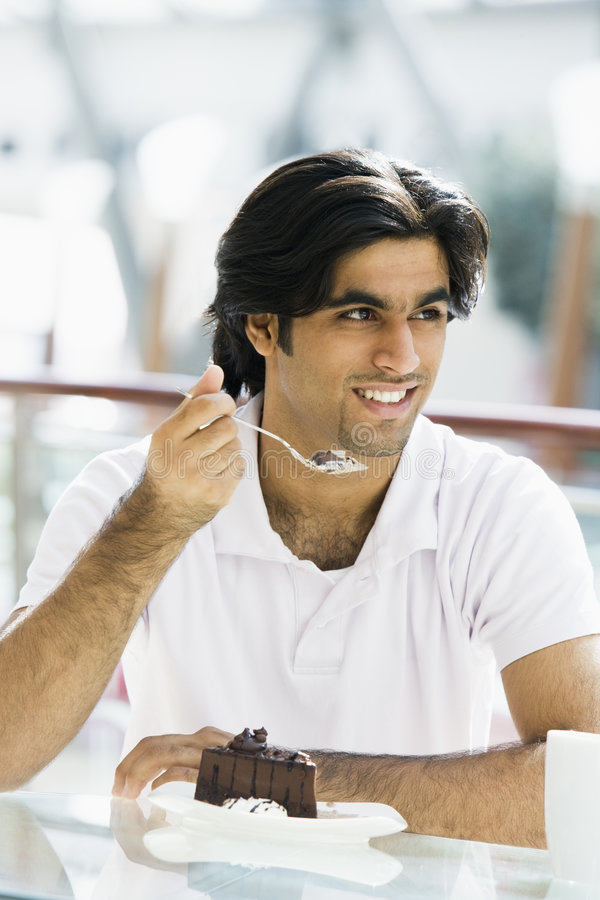Download Young Man Eating Cake In Cafe Stock Image - Image: 5210291