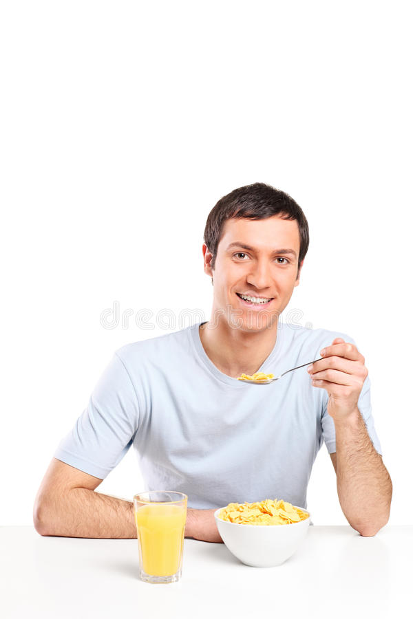 Young man eating cereal and drinking orange juice stock photo