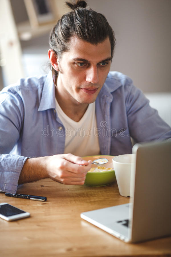 Young man eating corn flakes with milk and and looking to the laptop screen stock photos