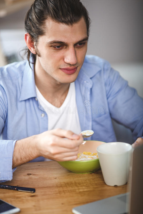 Young man eating corn flakes with milk and and looking to the laptop screen royalty free stock image