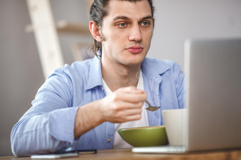 Young man eating corn flakes with milk and and looking to the laptop screen stock images
