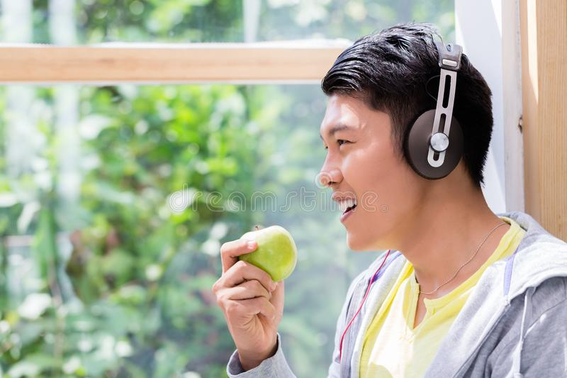 Young man eating a fresh green apple while listening to headphones stock image