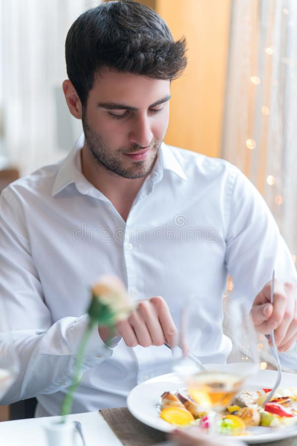 Young man eating a healthy food at restaurant. While talking with someone royalty free stock photo