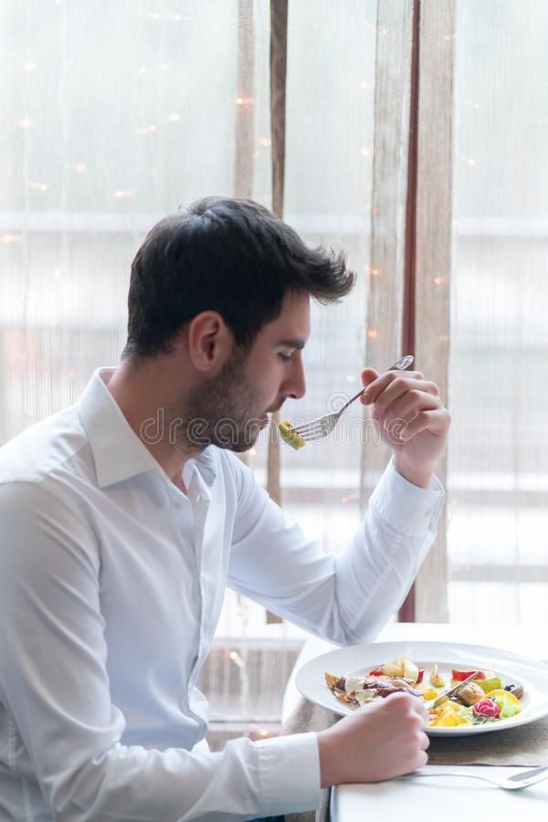 Young man eating a healthy food at restaurant. While talking with someone stock photo