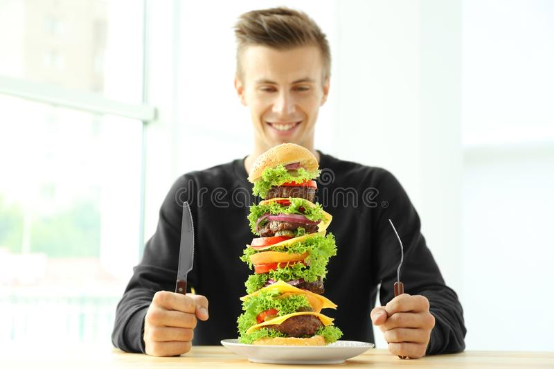 Man eating huge burger at table stock images
