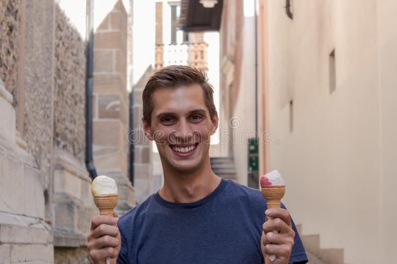 Young man eating ice cream in an alley stock image