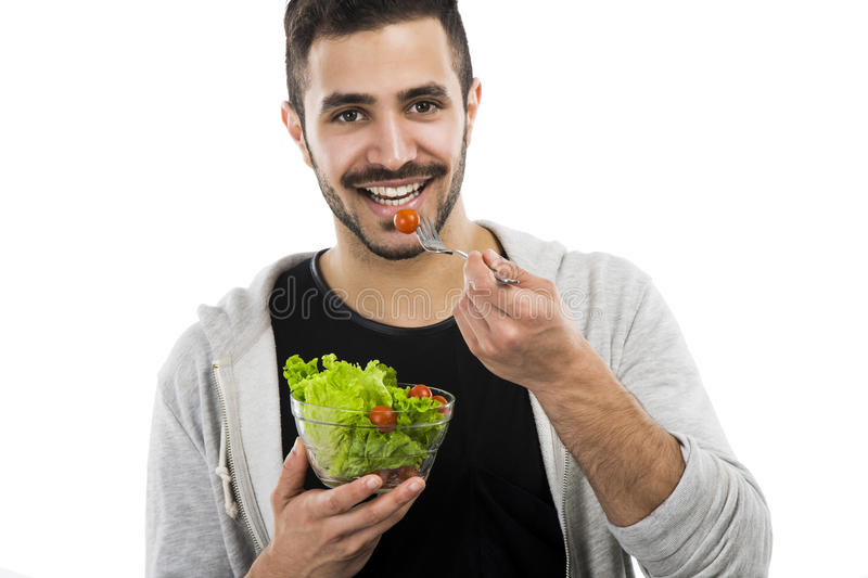 Young man eating a salad stock photos