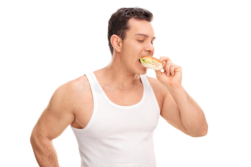 Young man eating a sandwich stock photography