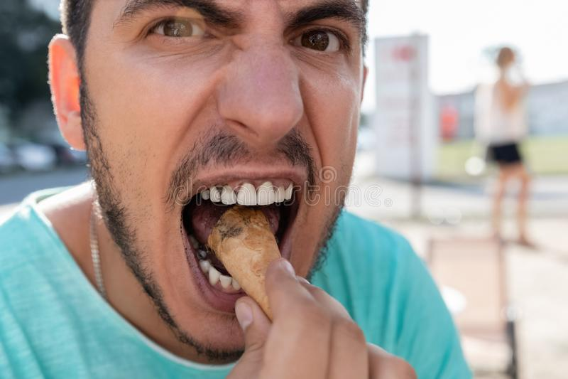 A young man eats black ice cream in a cone. stock photography