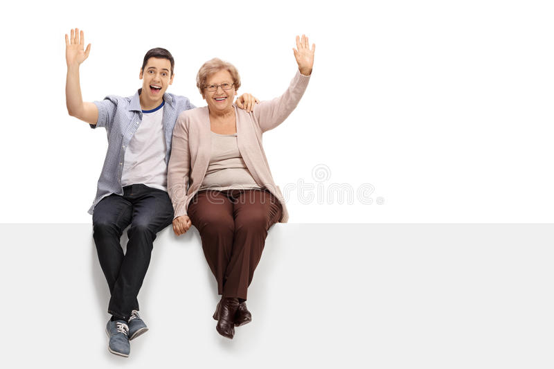 Young man and elderly woman sitting on panel and waving royalty free stock photo
