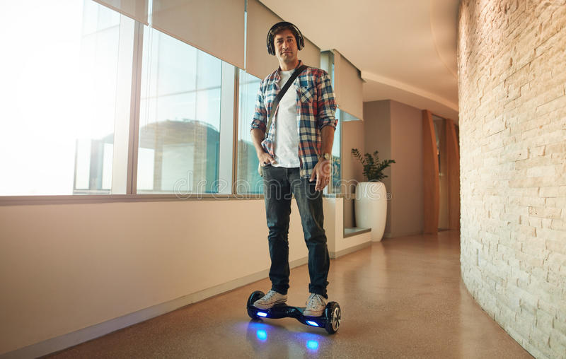 Young man on an electrical self-balancing scooter in office. Full length shot of stylish young man riding on electrical self-balancing scooter in modern office stock photo