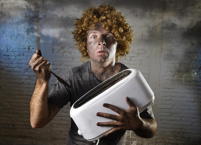 Young man electrocuted trying to get toast out of toaster with knife suffering domestic accident. And with dirty burnt face in funny shock expression screaming stock images
