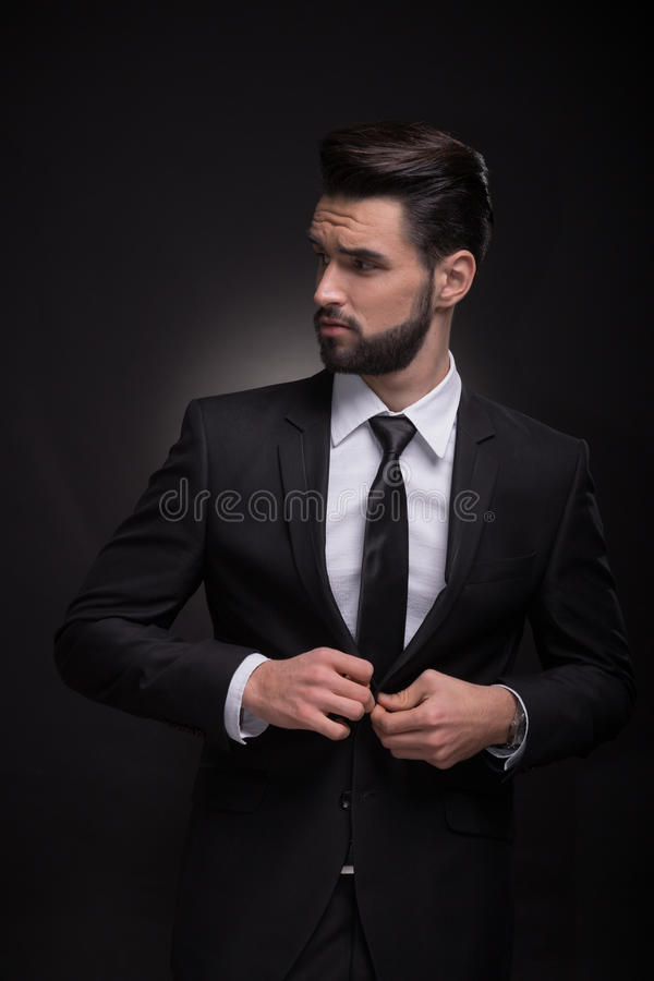 Young man elegant suit buttoning, looking sideways royalty free stock image