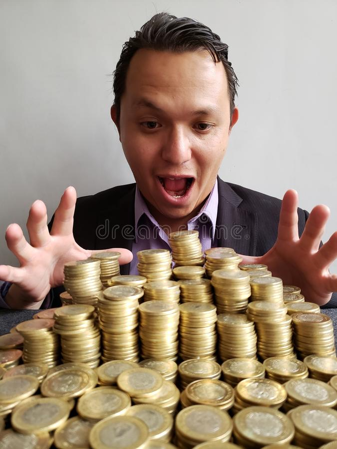 young man with emotion expression when looking at savings with the stacked coins of mexican pesos royalty free stock images
