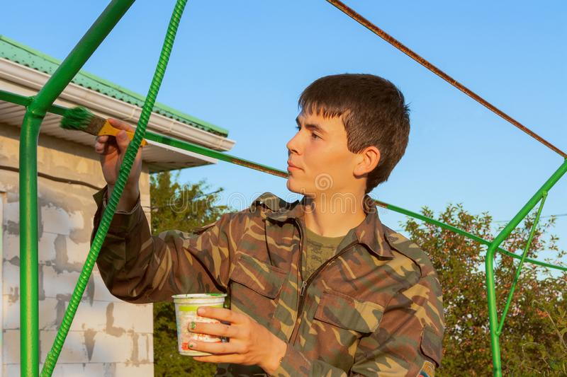 A young man, a man engaged in repair, painting a metal structure in the front garden stock photos