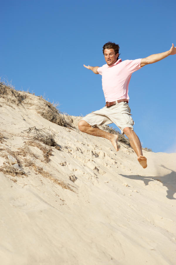 Download Young Man Enjoying Beach Holiday Running Down Dune Stock Photo - Image of male, seaside: 16297970