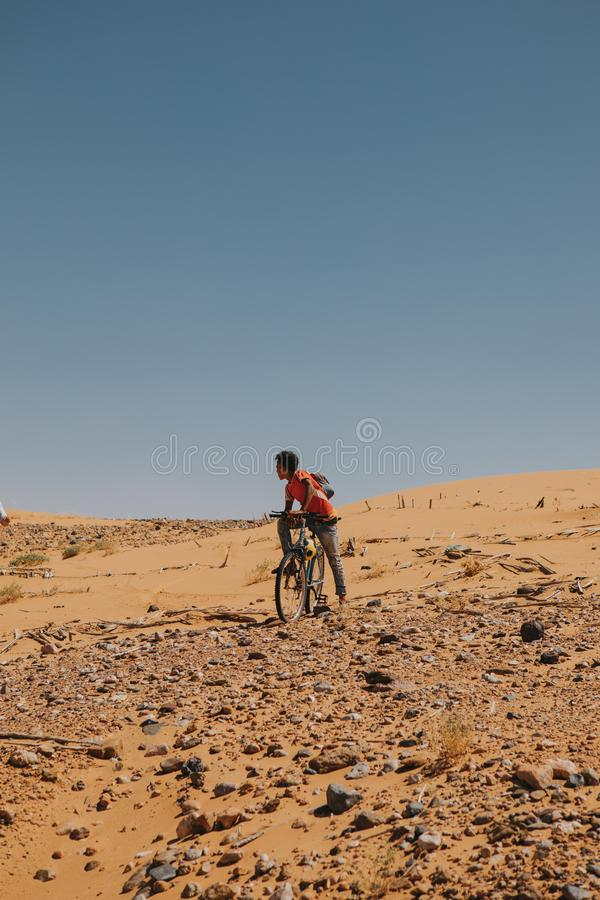 Young man enjoying a bicycle in Sahara desert. royalty free stock photos