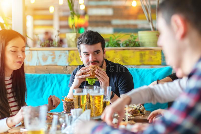 Young man enjoying burger and friends company at fast food restaurant stock image