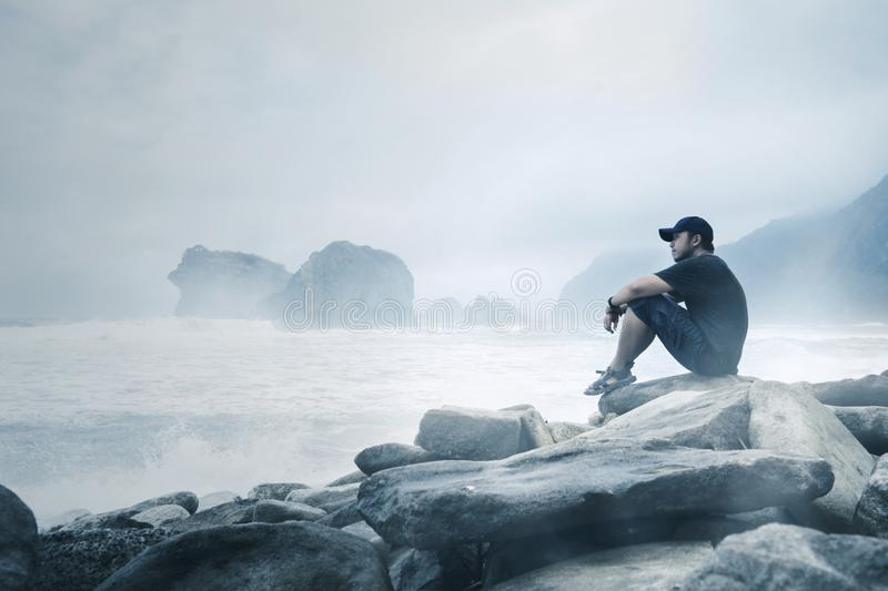 Young man enjoying a foggy Papuma beach view. Young man sitting on the stone while enjoying a foggy Papuma beach view at morning time royalty free stock image