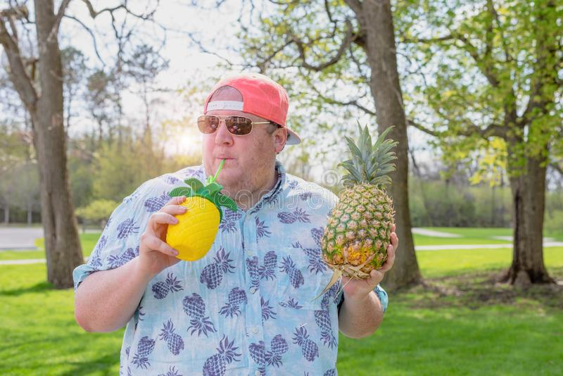 Young man enjoying a pineapple drink stock images