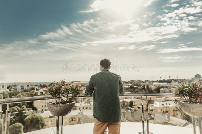 Young man enjoying the view from the balcony stock images