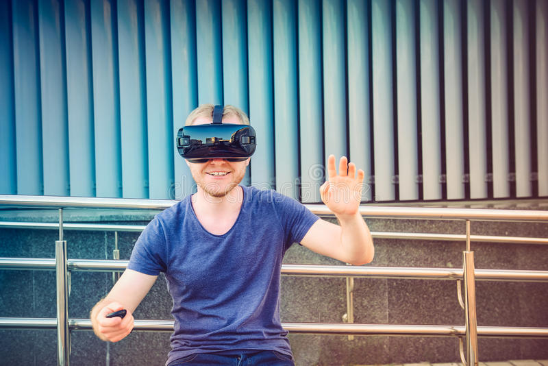 Young man enjoying virtual reality glasses headset or 3d spectacles on urban background outdoors. Technology, innovation, cyberspa stock image