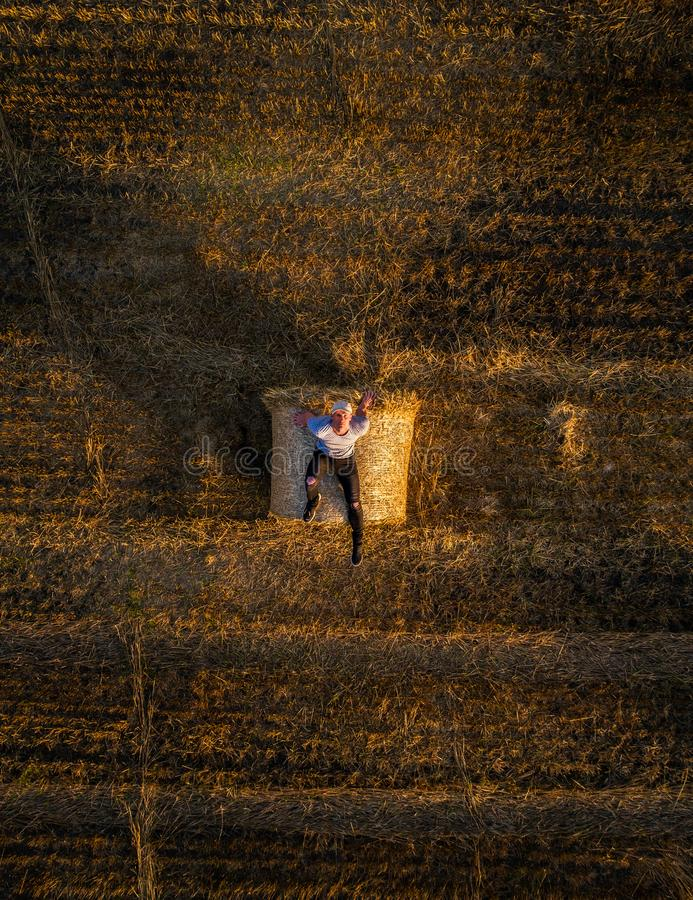 Young man enjoys sunset at the top of a hay bale royalty free stock image