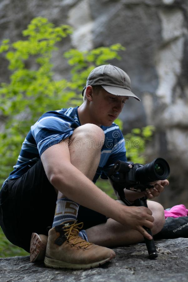 Young man entrepreneur taking a photography in a forest whilst sitting on a rock. Videomaker, stabalizer, proffesion, learbing, learning, skills royalty free stock photos