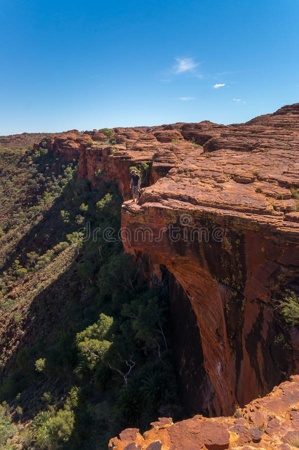 Young man enyoing view of the Kings Canyon and standing on the edge of a cliff, Watarrka National Park, Northern Territory,. View into the Kings Canyon, Watarrka royalty free stock photo