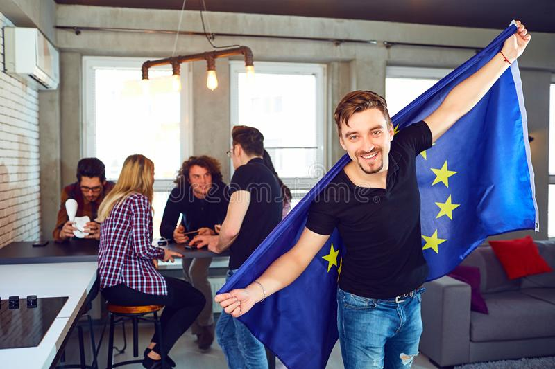 Young man with the european flag in his hands in the room. royalty free stock photo