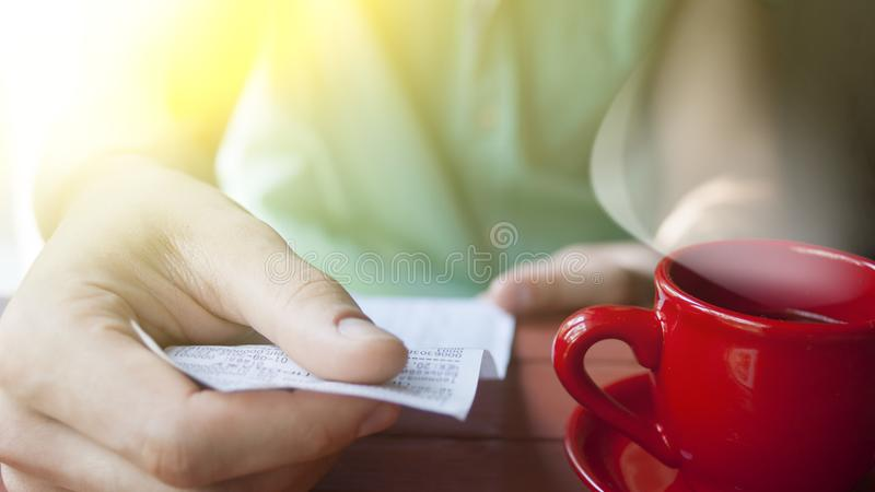 A young man examines the bill in a cafe on a Sunny summer morning stock photos