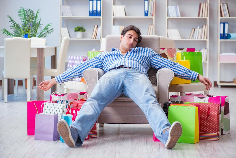 The young man after excessive shopping at home. Young man after excessive shopping at home royalty free stock images