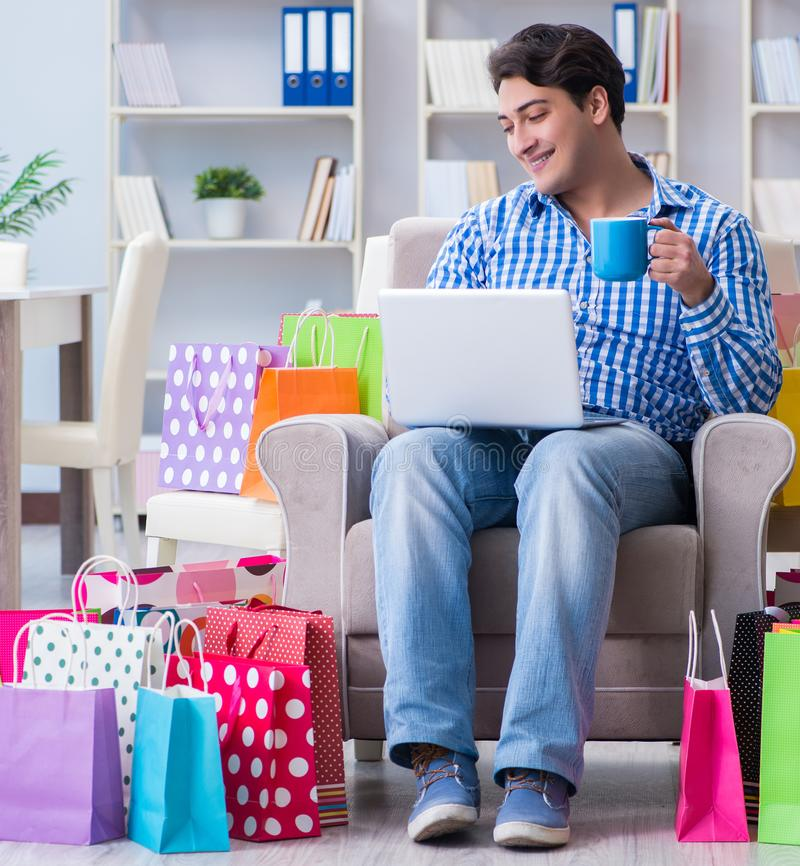 Young man after excessive shopping at home. The young man after excessive shopping at home royalty free stock photography