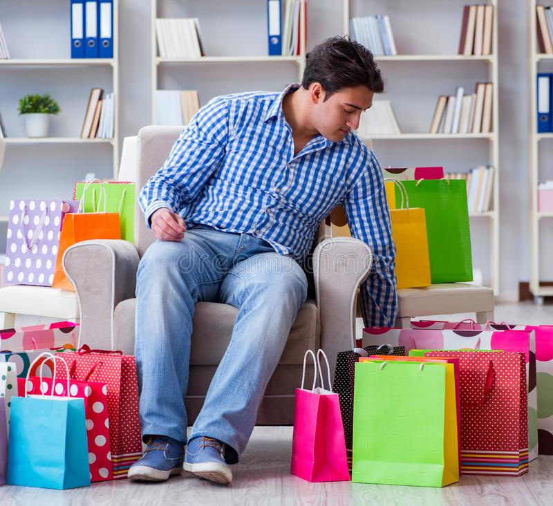 Young man after excessive shopping at home. The young man after excessive shopping at home stock image