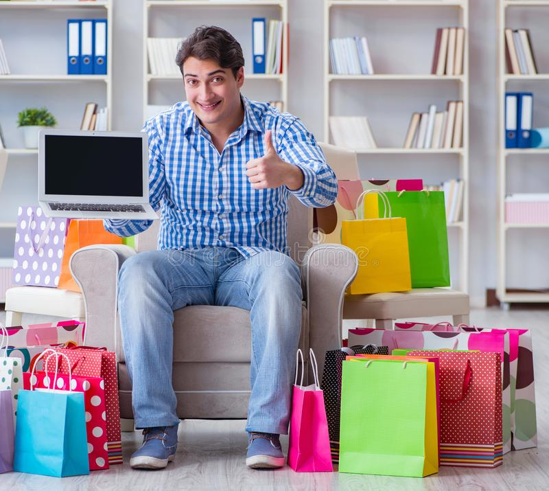 Young man after excessive shopping at home. The young man after excessive shopping at home stock photography