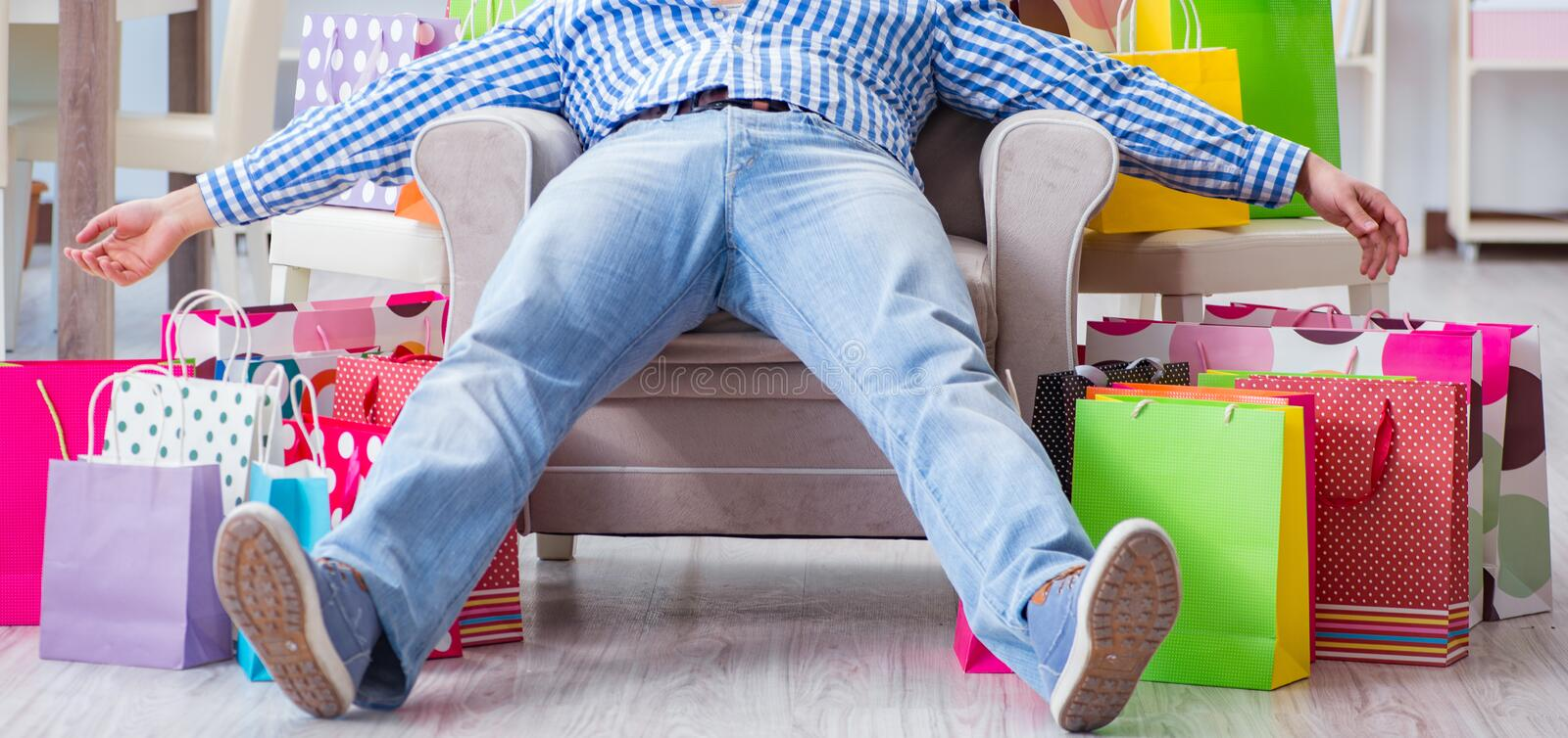 Young man after excessive shopping at home. The young man after excessive shopping at home stock photos