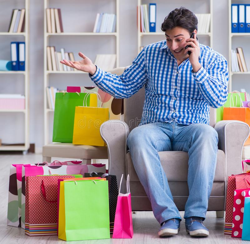 The young man after excessive shopping at home. Young man after excessive shopping at home stock image