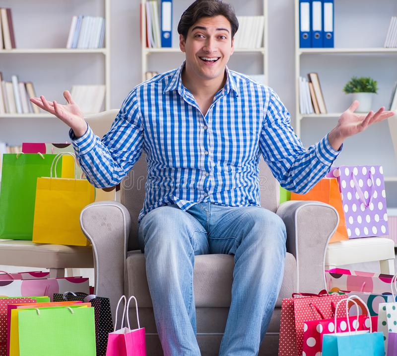Young man after excessive shopping at home. The young man after excessive shopping at home royalty free stock photos