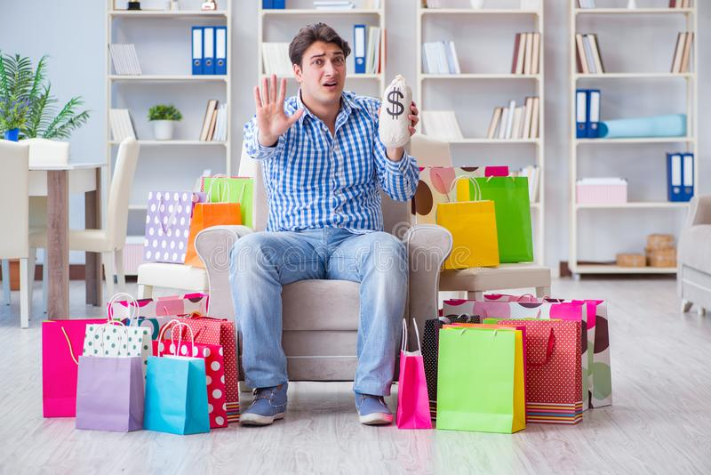 The young man after excessive shopping at home. Young man after excessive shopping at home royalty free stock photography