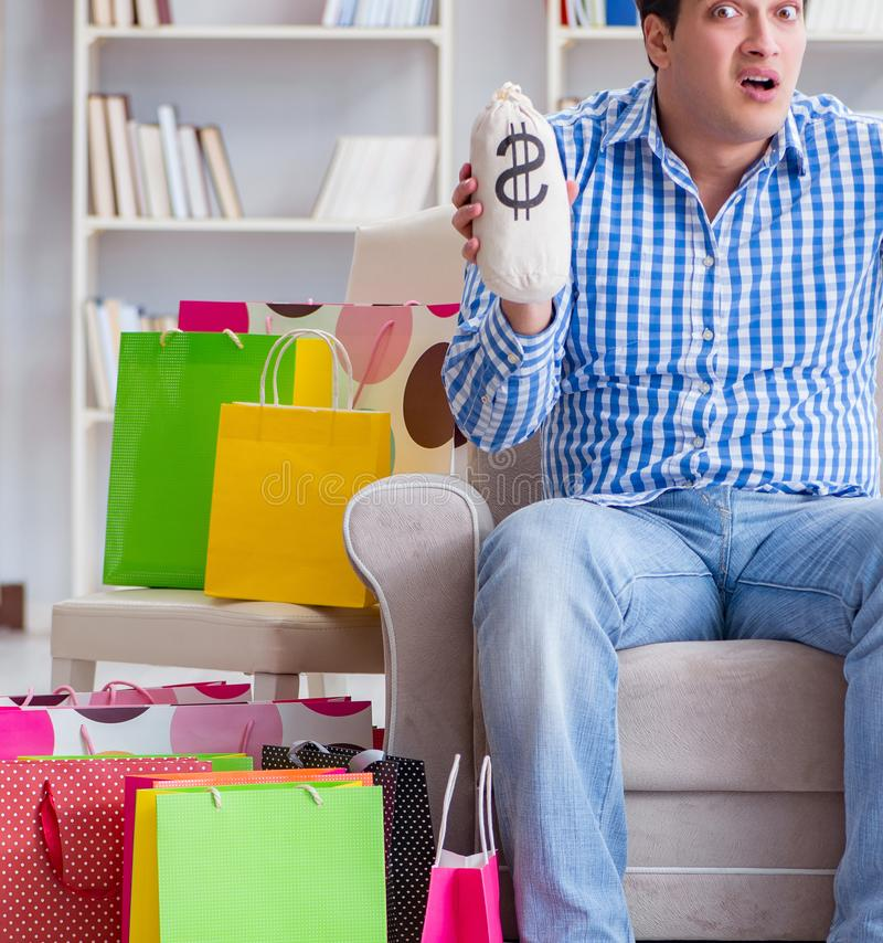 Young man after excessive shopping at home. The young man after excessive shopping at home royalty free stock image