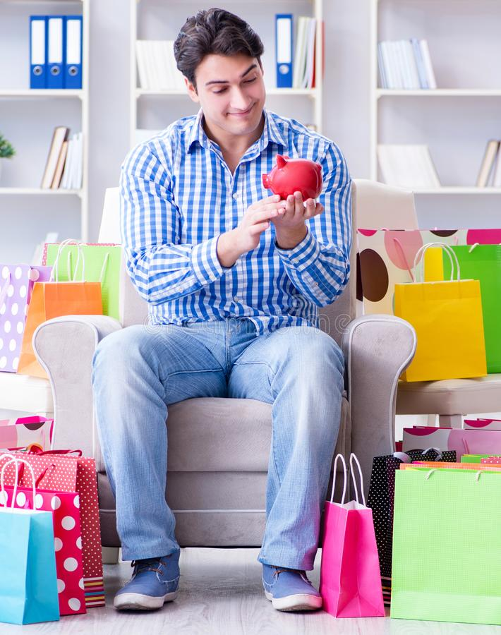 Young man after excessive shopping at home. The young man after excessive shopping at home royalty free stock photo
