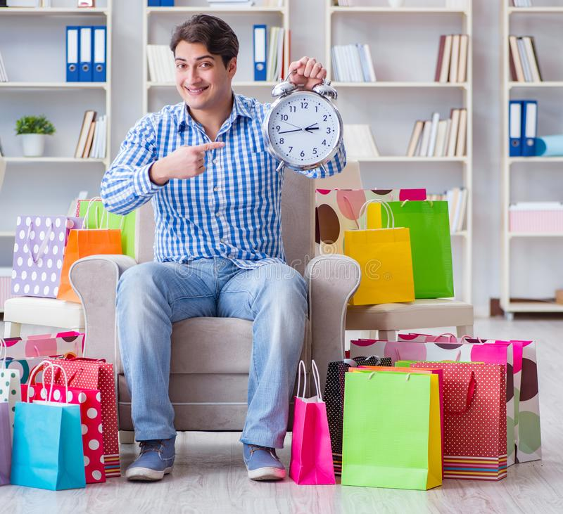 Young man after excessive shopping at home. The young man after excessive shopping at home royalty free stock images
