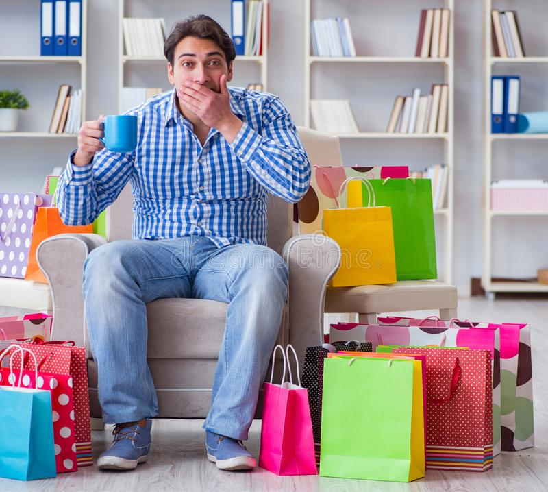 Young man after excessive shopping at home. The young man after excessive shopping at home stock images