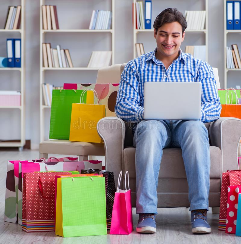 Young man after excessive shopping at home. The young man after excessive shopping at home stock photo