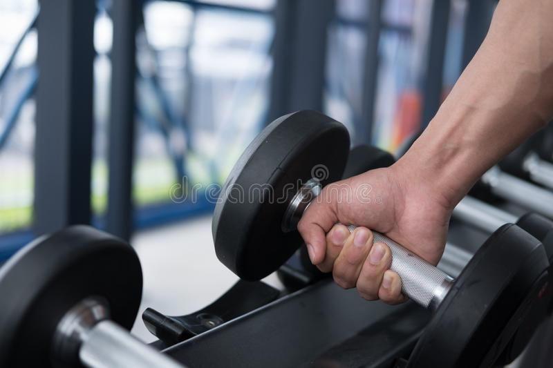 Young man execute exercise in fitness center. male athlete choose dumbbell in gym. sporty guy working out in health club. Young man execute exercise in fitness royalty free stock photography